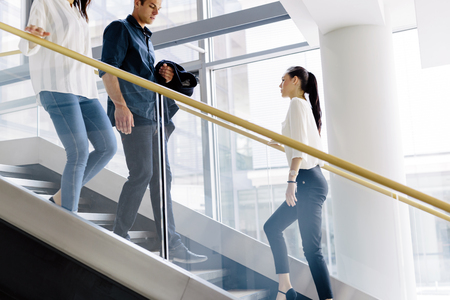 caucasian: Group of businessman walking and taking stairs in an office building Stock Photo