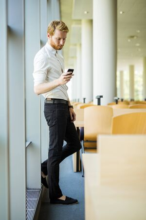 having a break: Relaxed businessman having a break and looking at his phone