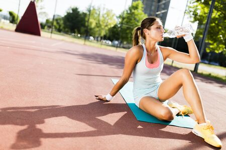 tomando agua: Young beautiful woman drinking water after exercise in a city training court on a sunny day