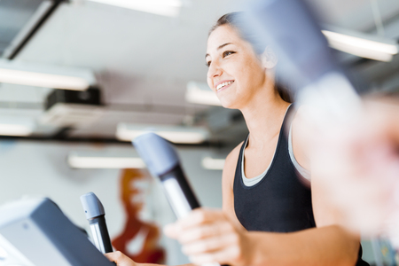 Beautiful young lady using the elliptical trainer in a gym in a positive mood
