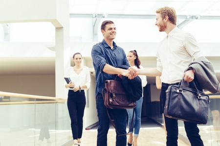 cheerfully: Businessmen shaking hands and greeting each other cheerfully