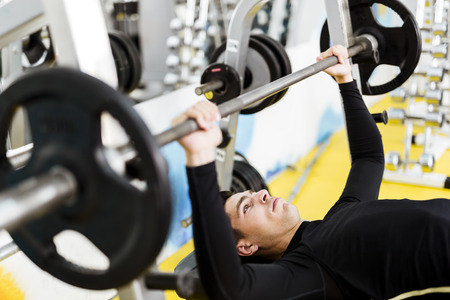 well build: Closeup of young handsome male doing exercises on a bench press