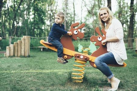 Moeder en zoon spelen in de speeltuin en rijdt op een wip Stockfoto