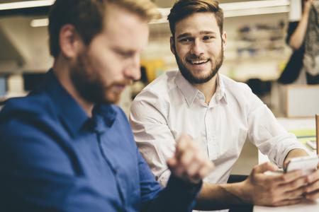 personas platicando: Hombres hermosos que trabajan en una oficina y sonriente