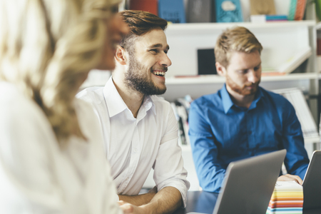personas sentadas: Compañeros alegres en la oficina durante la reunión de la empresa