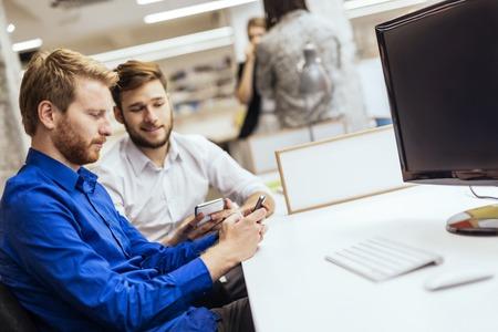 hombres guapos: Hombres hermosos que trabajan en una oficina y sonriente