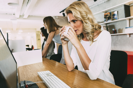 stay alert: Beautiful businesswoman drinking tea to stay alert and focused at work