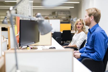 monitor de computadora: Hermosa rubia sentada en una oficina y trabajar y hablar con un colega Foto de archivo
