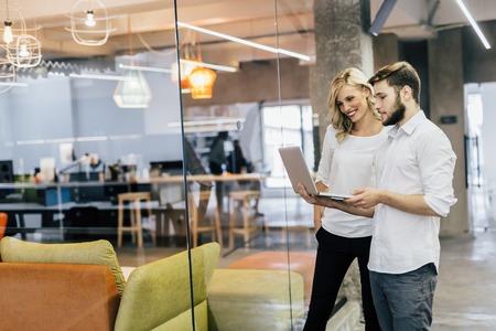 reunion de trabajo: Cowerkers mirando portátil en una oficina moderna