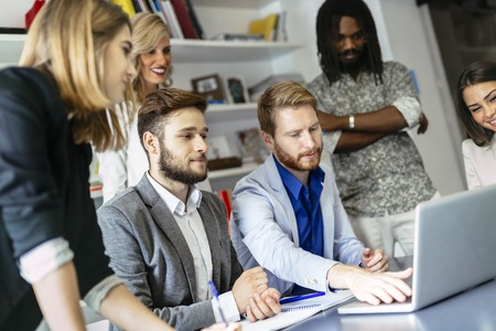 Kollégák brainstorming hivatalban, rámutatva ugyanakkor az új ötletek laptop