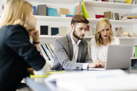 reuniones empresariales: Empresaria y hombre de negocios que trabajan en oficina junto con los compañeros de trabajo sentado en la mesa