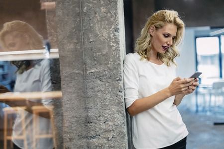 woman on phone: Beautiful blonde woman texting on cell phone