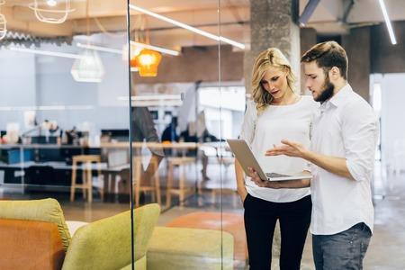 Discussing new ideas with a coworker in a beautiful modern office Stock Photo