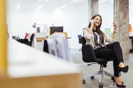persona llamando: Mujer de negocios confidente que usa el teléfono en una oficina Foto de archivo