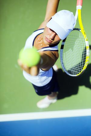 sexo femenino: Jugador de tenis de sexo femenino hermoso que sirve al aire libre y un primer plano del saque desde arriba Foto de archivo