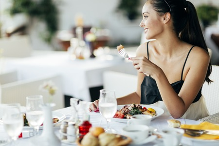 smiling: Beautiful woman eating meal in restaurant during sunset