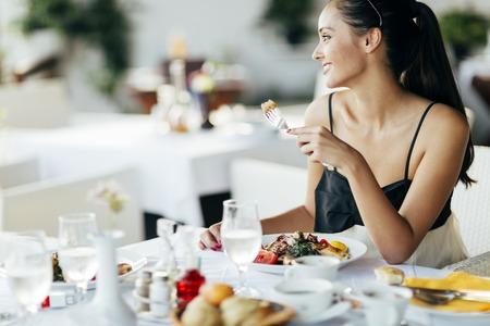 chicas sonriendo: Hermosa mujer de comer comida en el restaurante durante la puesta del sol