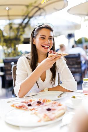 comiendo: Hermosa mujer joven comer una rebanada de pizza en un restaurante al aire libre