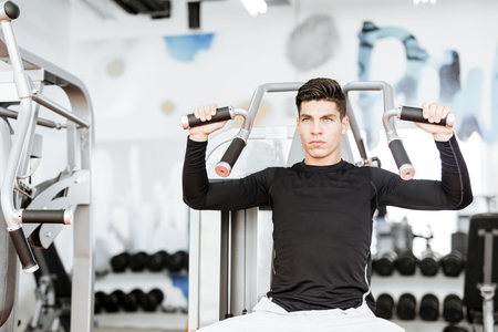 looking towards camera: Portrait of a handsome young man training in a gym and looking towards the camera