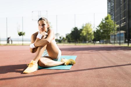 taking a break: Portrait of a young beautiful fit sportswoman in the city taking a break