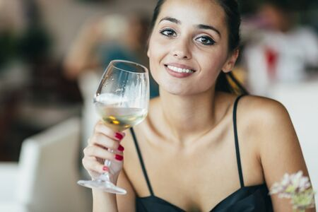 copa de vino: Mujer hermosa que prueba el vino mientras se est� sentado en el restaurante