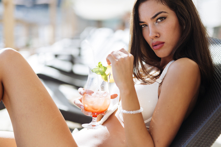 Portrait of sunbathing model with cocktail in her hand