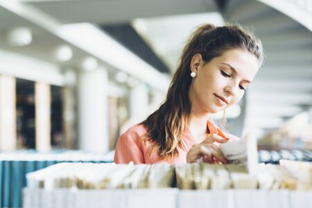 choose university: Beautiful female student takes the right book off the shelf Stock Photo