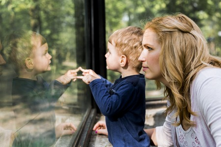 family with two children: Beautiful woman holding her son with his reflection on showing