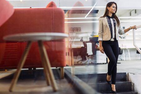 mujer elegante: Mujer hermosa que usa las escaleras en una oficina y sonriendo