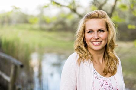Mooie jonge vrouw poseren en glimlachen buiten tijdens de zonnige zomerdag Stockfoto