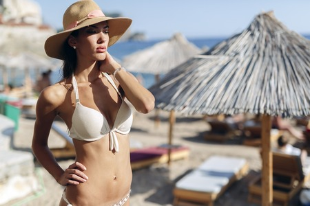 cute girl with long hair: Beautiful brunette wearing hat on beach and posing