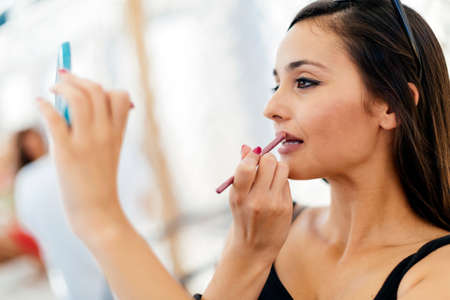applying lipstick: Beautiful woman applying lipstick
