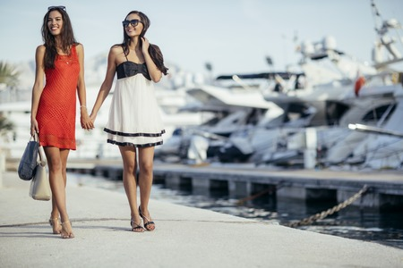 Vida de lujo para dos mujeres caminando y compras en una bahía