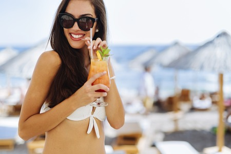 sexy female body: Attractive brunette drinking cocktails on beach and enjoying her vacation