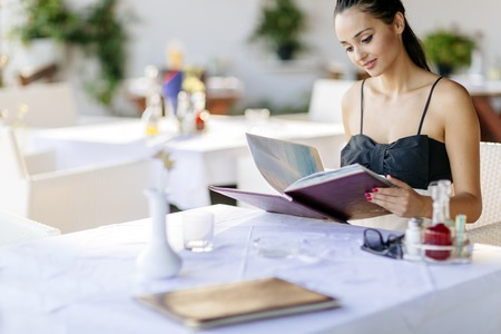 what to eat: Beautiful woman ordering from menu in restaurant and deciding what to eat