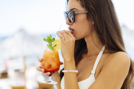 tropical drink: Attractive woman drinking cocktail, shot taken from side. Stock Photo