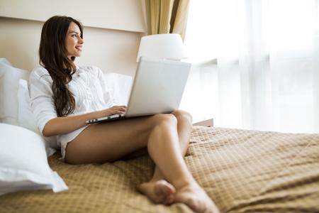 femme brune sexy: Belle jeune femme avec de longues jambes sexy en chemise en utilisant un ordinateur portable dans le lit