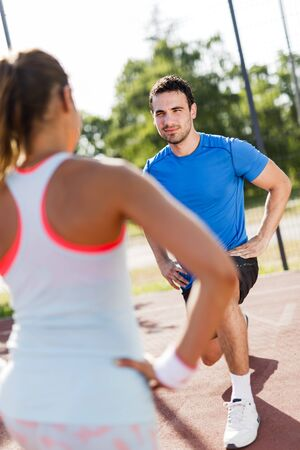 facing each other: Young athletic man and woman stretching outdoors on a hot summer day facing each other