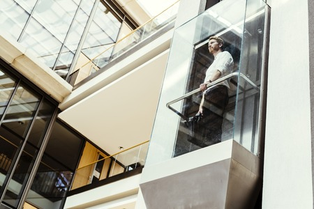 Businessman taking modern glass elevator to the upper floors Stock Photo