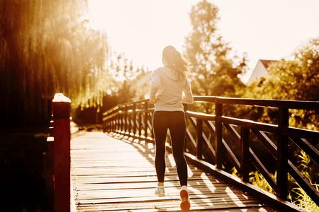 female jogger: Beautiful female jogger running during sunset across bridge