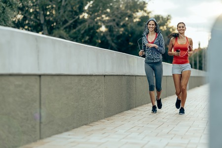 jogging: Women jogging in city in dusk and improving their stamina while losing weight