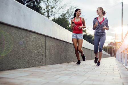 Twee vrouwen die de uitoefening van joggen in de stad, terwijl de zon ondergaat