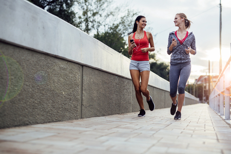 lifestyle outdoors: Two women exercising by jogging in the city while sun is setting Stock Photo