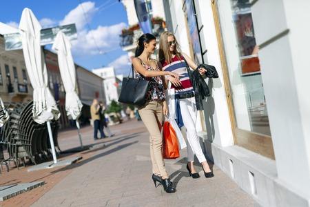 Beautiful women shopping spree on street Imagens