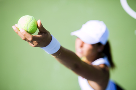 competitions: Beautiful female tennis player serving outdoor and a closeup of the serve from above