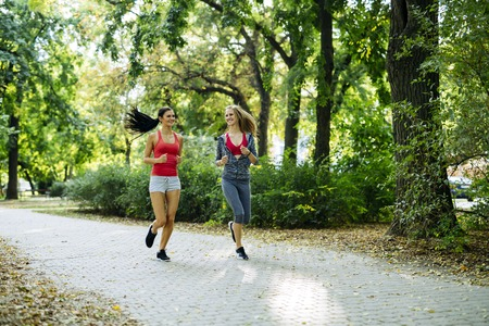 staying fit: Young fit women jogging outdoors and staying fit