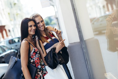 charming woman: Beautiful women shopping outdoors and holding bags Stock Photo