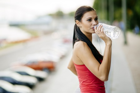 recuperate: Thirsty woman drinking water to recuperate after jogging