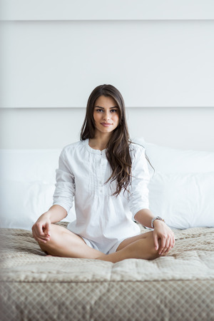 tailor seat: Beautiful brunette in a white shirt tailor seat posing on a bed and relaxing
