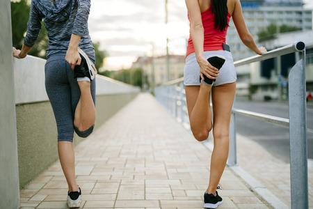 hacer footing: Dos mujeres estirar los pies antes de correr